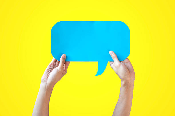Human Hands Holding Blue Speech Bubble Over Yellow Background stock photo