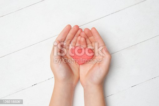 Human hands holding, giving heart isolated on white wooden background. Concept of emotions, feelings, charity, family, supporting hand. Thankful, inspirational. Romantic and togetherness.