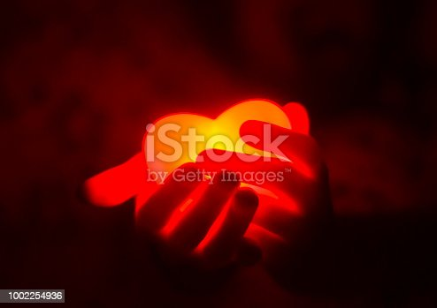 istock Human hands holding red glowing heart in the dark 1002254936