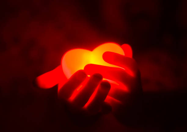 human hands holding red glowing heart in the dark - passion stock pictures, royalty-free photos & images