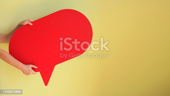 626645552 istock photo Human Hands Holding Red Speech Bubble Over Yellow Background 1248325894