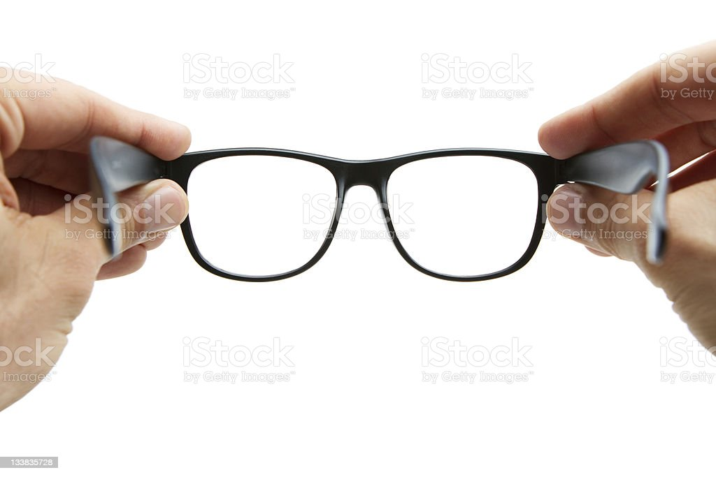 Human hands holding retro style eyeglasses stock photo