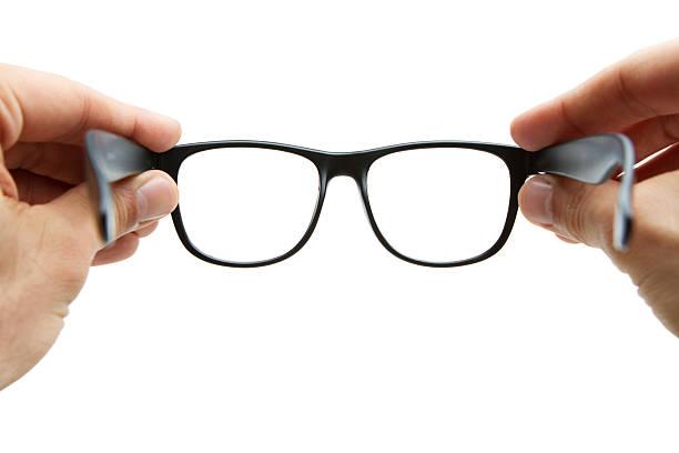 human hands holding retro style eyeglasses - gözlük stok fotoğraflar ve resimler