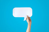 istock Human Hands Holding White Speech Bubble Over Blue Background 626645552