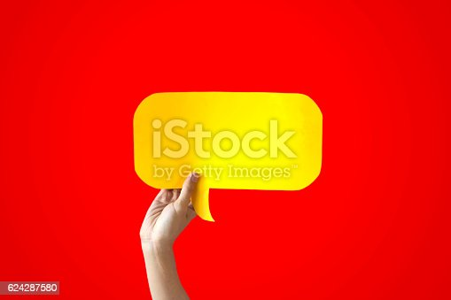 istock Human Hands Holding Yellow Speech Bubble Over Red Background 624287580