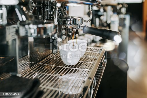 Human hands making good quality espresso coffee drink. Professional working at coffee shop.