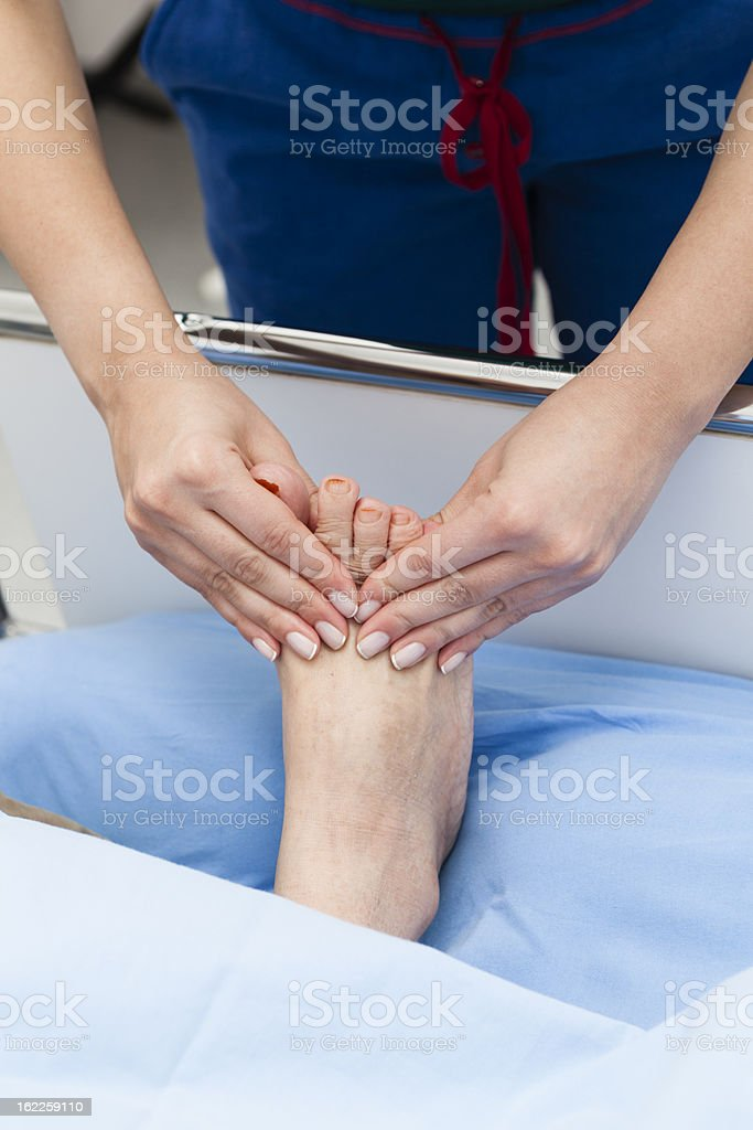 Human hands massaging a woman's foot royalty-free stock photo