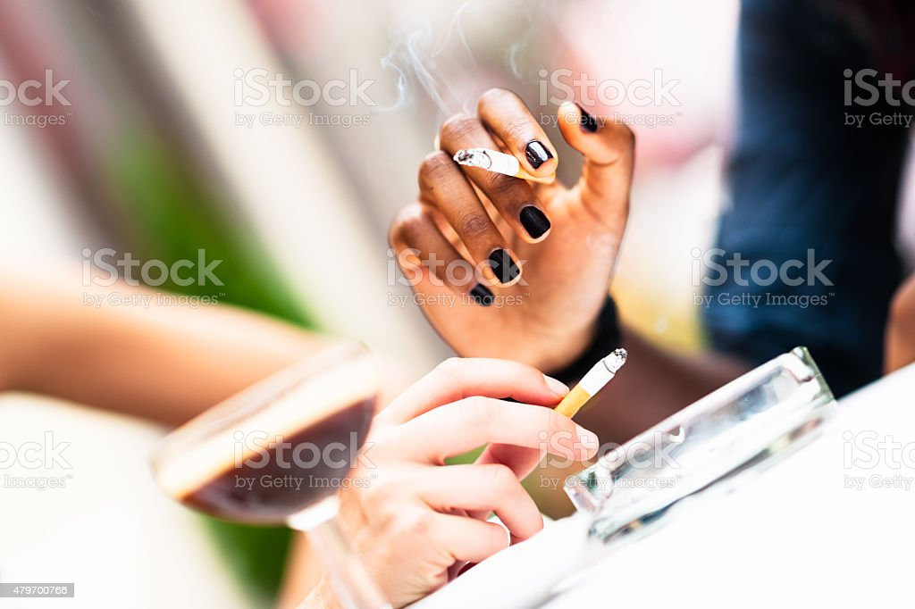 Human hands of two different ethnicity woman holding cigarettes stock photo