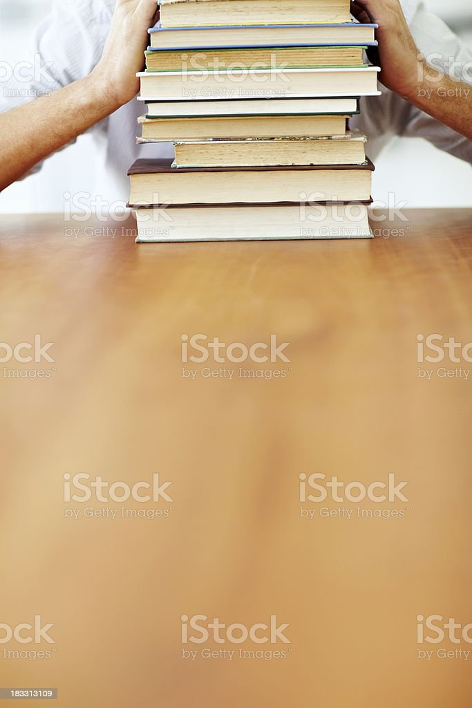 Human hands on pile of books with desk in foreground royalty-free stock photo