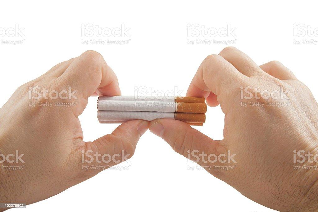 Human hands preparing to break stack of cigarettes stock photo