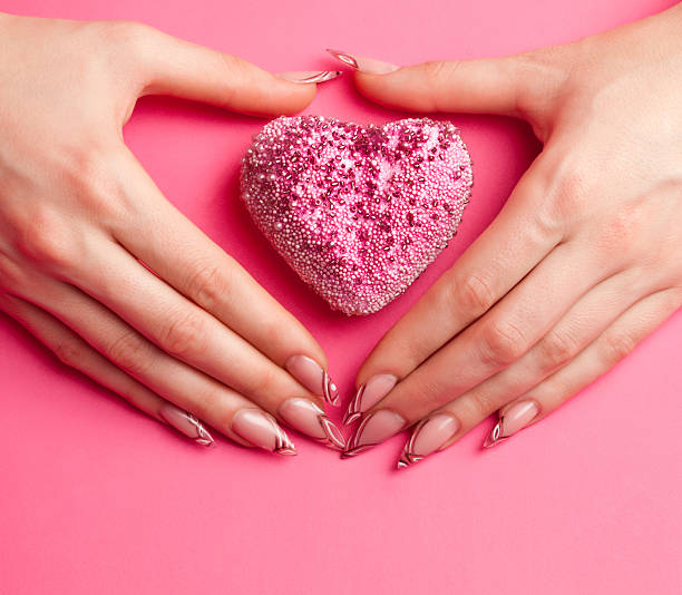 Human hands with beautiful manicure folded in shape of heart stock photo