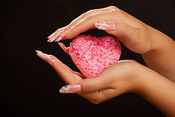 Human hands with beautiful manicure hold pink heart stock photo