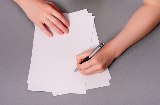 818512928 istock photo Human hands with pencil writing on paper and erase rubber on wooden table background 855993888