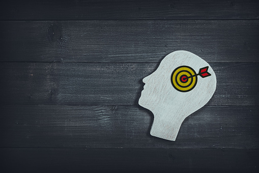 istock Human head and face with dartboard  sign  on wood table background. Brain of thinking about target and strategy , Symbol of Process and Positive Mind concept 1166844695
