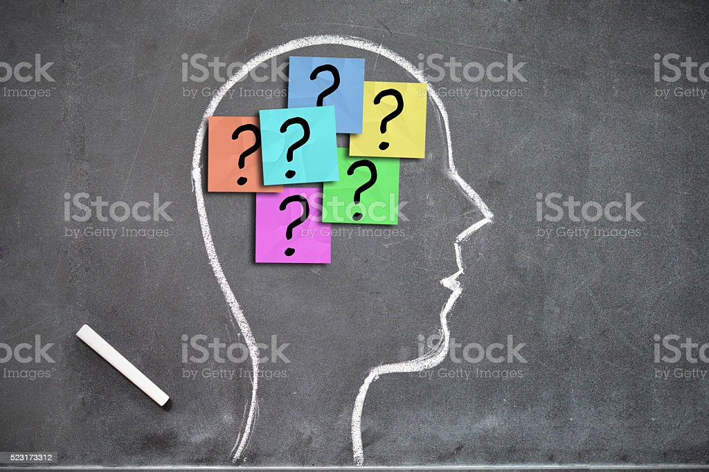 Human head shape with lots of question marks on stickers stock photo