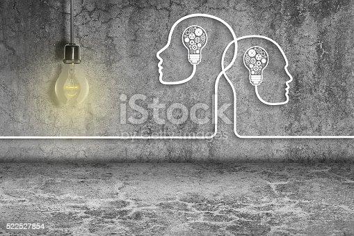 istock Human heads with light bulbs and gears on dirty wall 522527854
