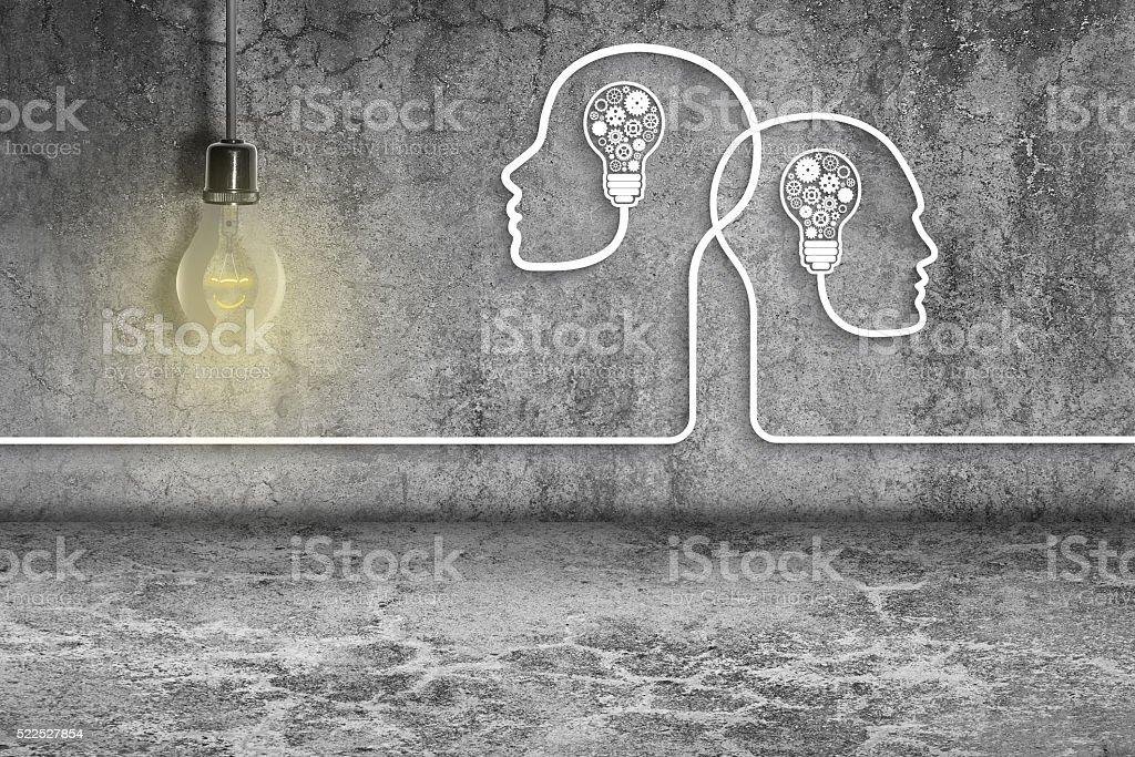 Human heads with light bulbs and gears on dirty wall stock photo