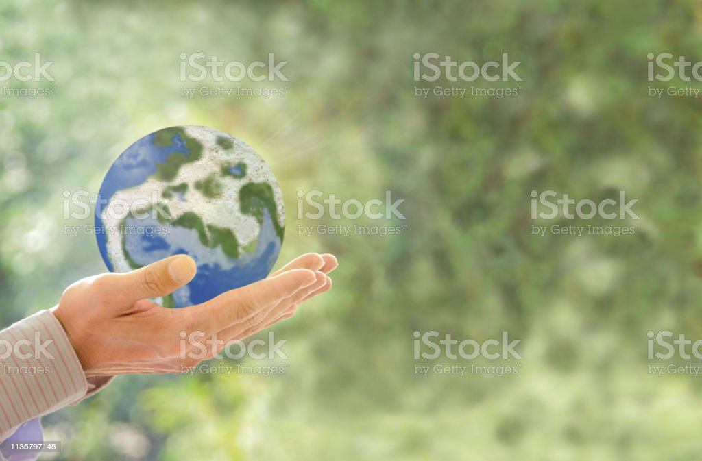 Human holding Earth in hands against green spring background and sun...