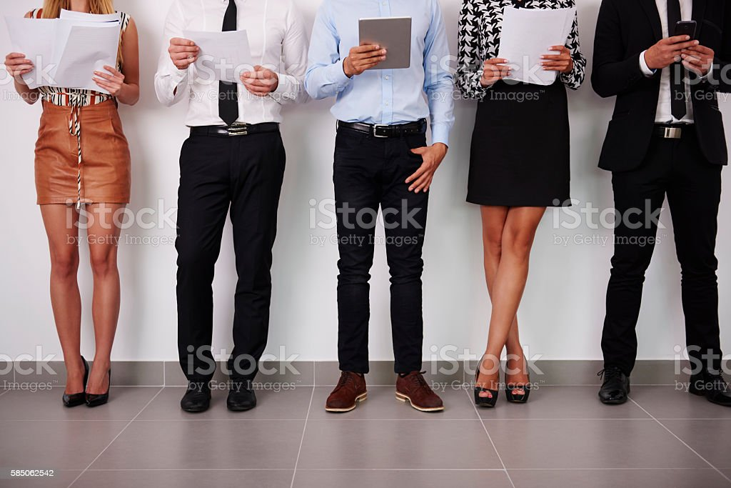 Human legs of people which waiting for job interview stock photo