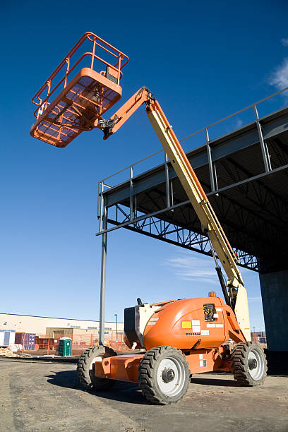 Human Lift An orange human lift sitting outide a newly constructed building mobile crane stock pictures, royalty-free photos & images