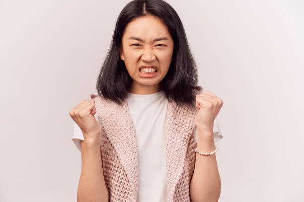 human looses temper, clenches teeth wrinkles nose Portrait of irritated human looses temper, clenches teeth from anger, wrinkles nose, looks with hate at camera. Woman Asian appearance brown eyes stands isolated white background in Studio clenching teeth stock pictures, royalty-free photos & images