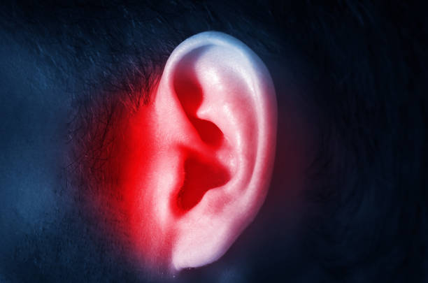 human male ear on a dark background isolated - ear stock photos and pictures