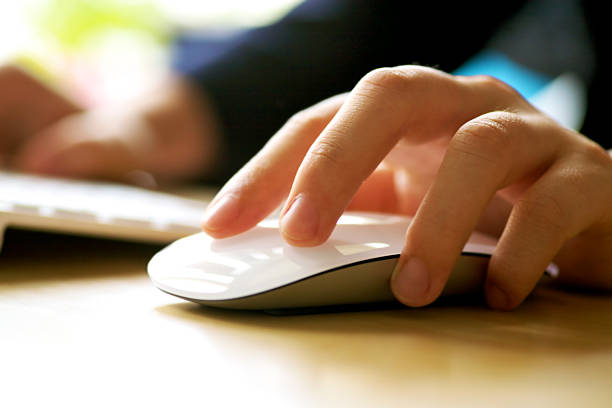 a human operating a computer mouse - computer mouse stock photos and pictures