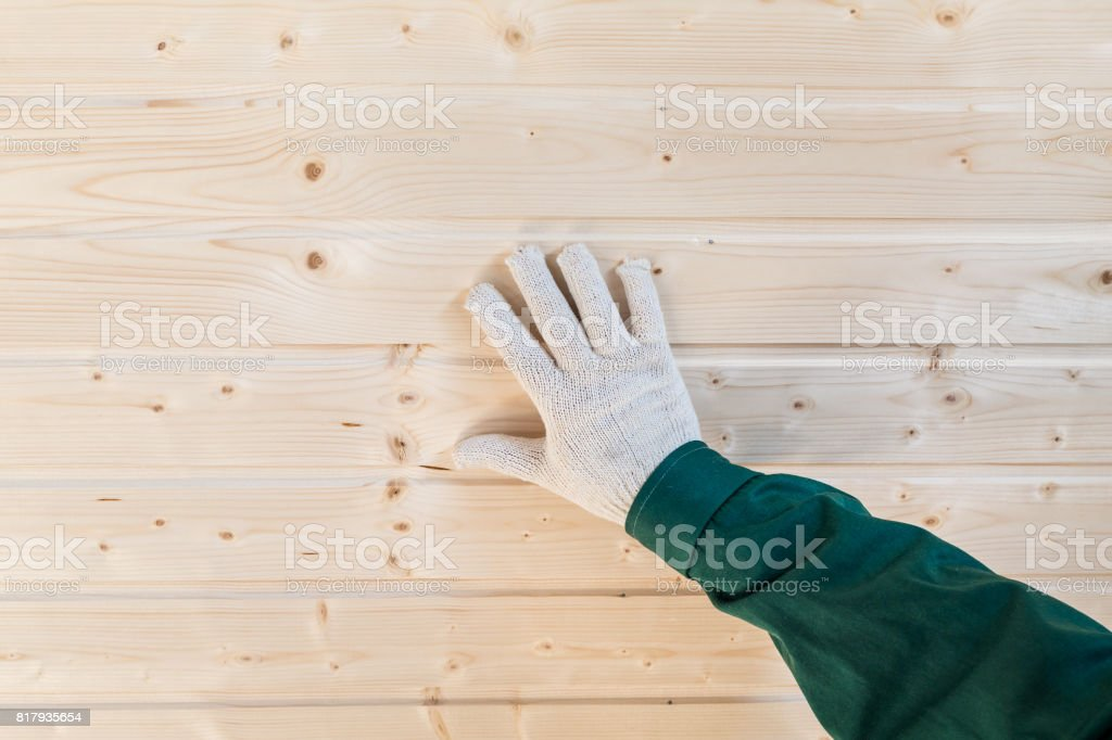 Palm humaine dans les gants sur le mur de languette et rainure - Photo