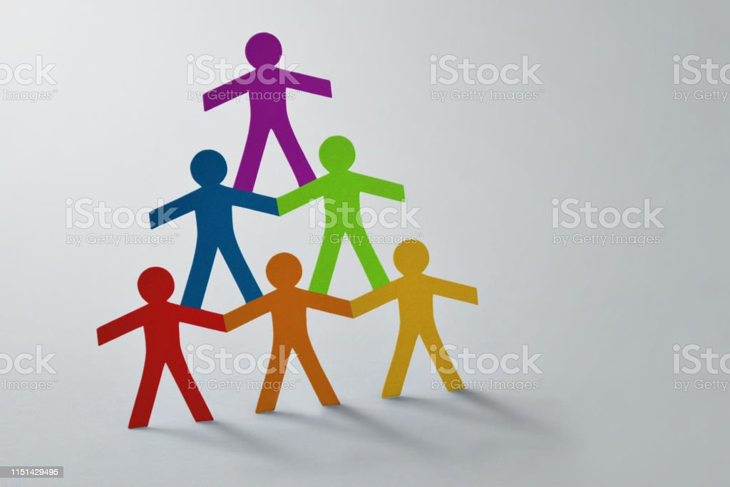 Human pyramid of colorful paper cut-out people on white background -...