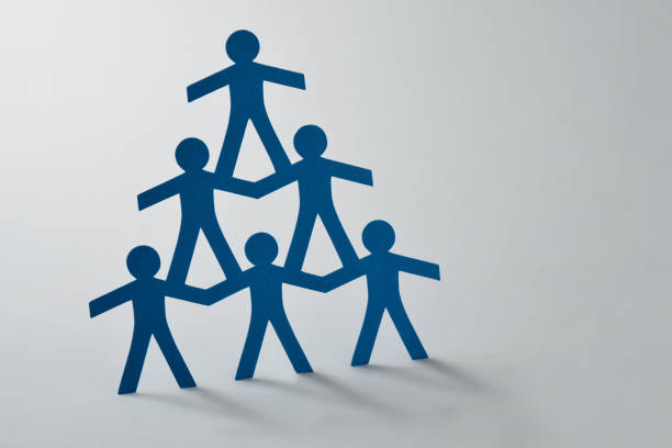 Human pyramid of paper cut-out people on white background - Concept of teamwork Human pyramid of paper cut-out people on white background - Concept of teamwork labor union stock pictures, royalty-free photos & images