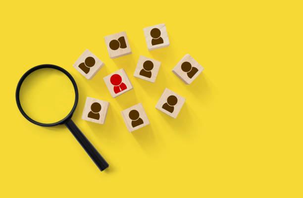 mänsklig resurs- och talent management och rekrytering företag byggnad laget, personlig utveckling för medarbetare i organisationen. trä kub block på gul bakgrund med förstoringsglas - stötta beskrivande position bildbanksfoton och bilder