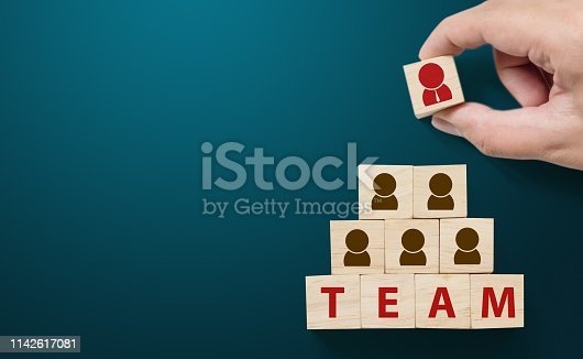 istock Human resource management and recruitment business team concept, Hand putting wood cube block on top pyramid 1142617081