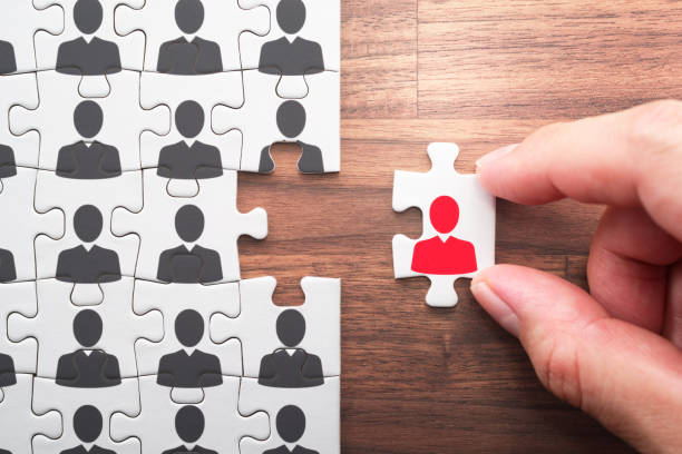 Human resource management. Selecting person for the job. Personnel, employment and recruitment concept. Assembling jigsaw puzzle pieces on wood desk. applicant stock pictures, royalty-free photos & images