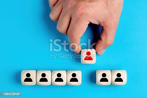 Human resources and employment concept. Male hand arranging wooden blocks with manager and staff icons.
