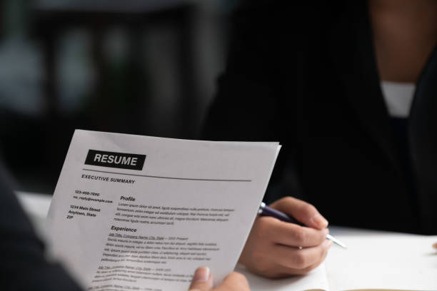 Human resources department manager reads CV resume document of an employee candidate at interview room. Job application, recruit and labor hiring concept. stock photo