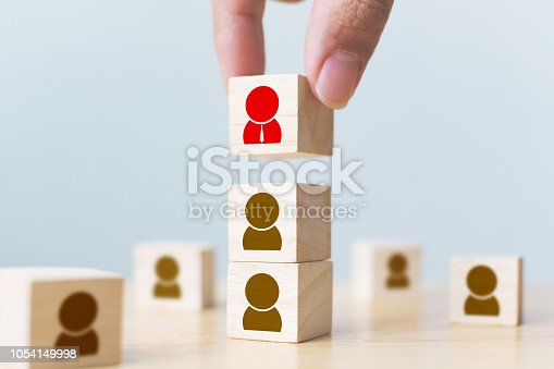 641422198istockphoto Human resources management and recruitment business build team concept. Hand putting wood cube block on top with icon 1054149998