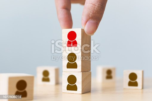 641422198istockphoto Human resources management and recruitment business build team concept. Hand putting wood cube block on top with icon 1072506014