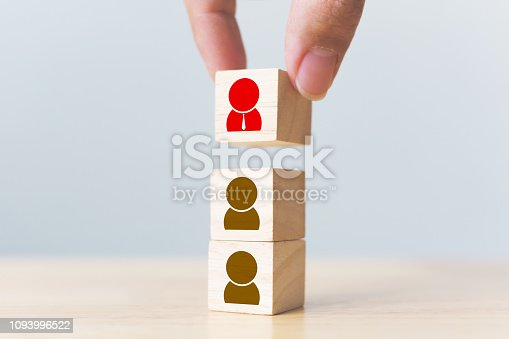 641422198istockphoto Human resources management and recruitment business build team concept. Hand putting wood cube block on top with icon 1093996522