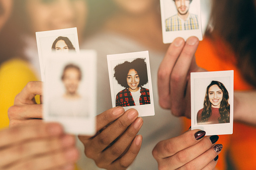 A group of people holding photos of themselves.