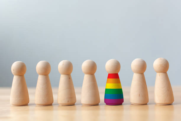 Human rights of LGBT campaign concept. Wooden dolls with rainbow colors are different stand out from crowd Human rights of LGBT campaign concept. Wooden dolls with rainbow colours are different stand out from crowd sex discrimination stock pictures, royalty-free photos & images