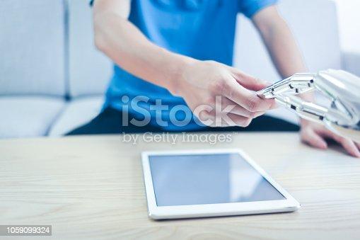 istock Human shaking hands with robot indoors 1059099324