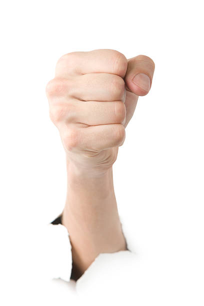 Human showing fist through the paper stock photo