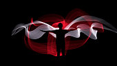 Picture of Human silhouette against red and white backlight in shape of wings. Light painting photography. Long exposure.