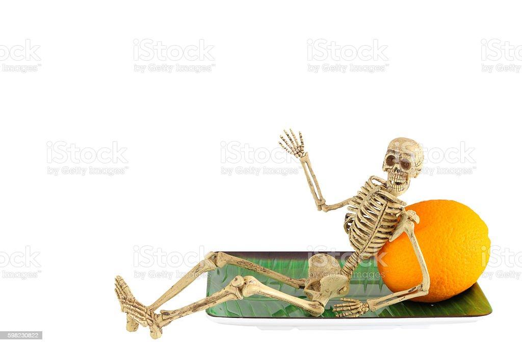 Human skeleton leaning on orange, relaxing foto royalty-free