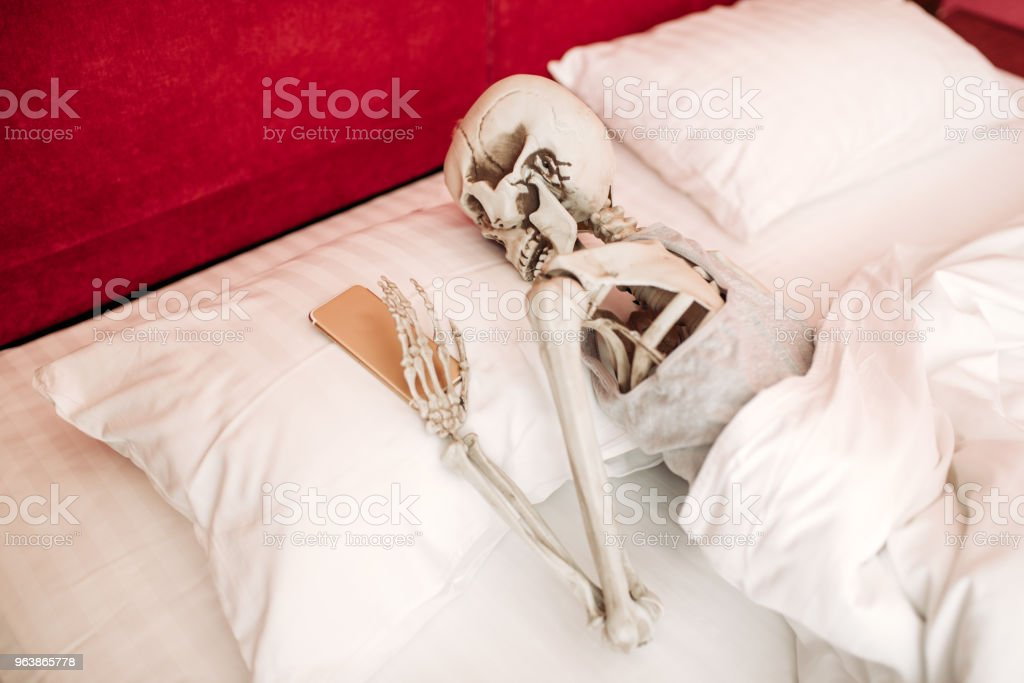 Human skeleton with phone in hand lies in bed - Royalty-free Bedroom Stock Photo