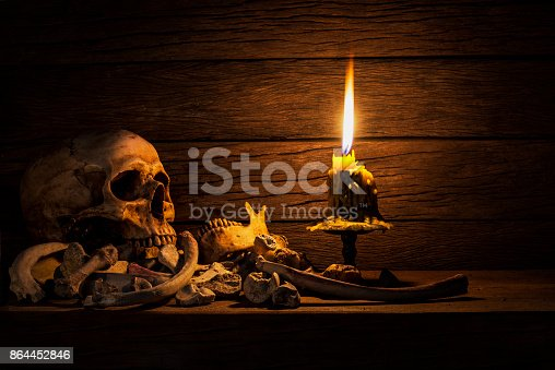 istock Human skull and pile bone with candle Light, Still life style onold wooden table 864452846