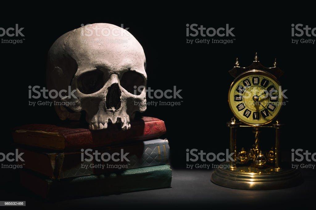 Cráneo humano en viejos libros cerca reloj vintage retro sobre fondo negro en el haz de luz. Concepto dramático. - foto de stock