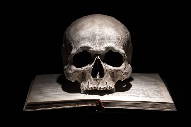 Cráneo humano en viejo libro abierto sobre fondo negro. Concepto dramático. - foto de stock