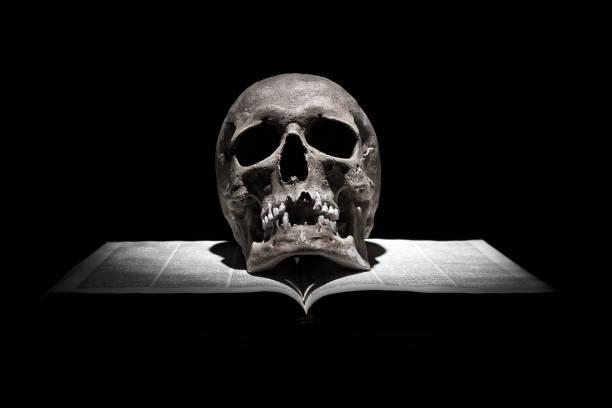 Cráneo humano en viejo libro abierto sobre fondo negro en el haz de luz - foto de stock