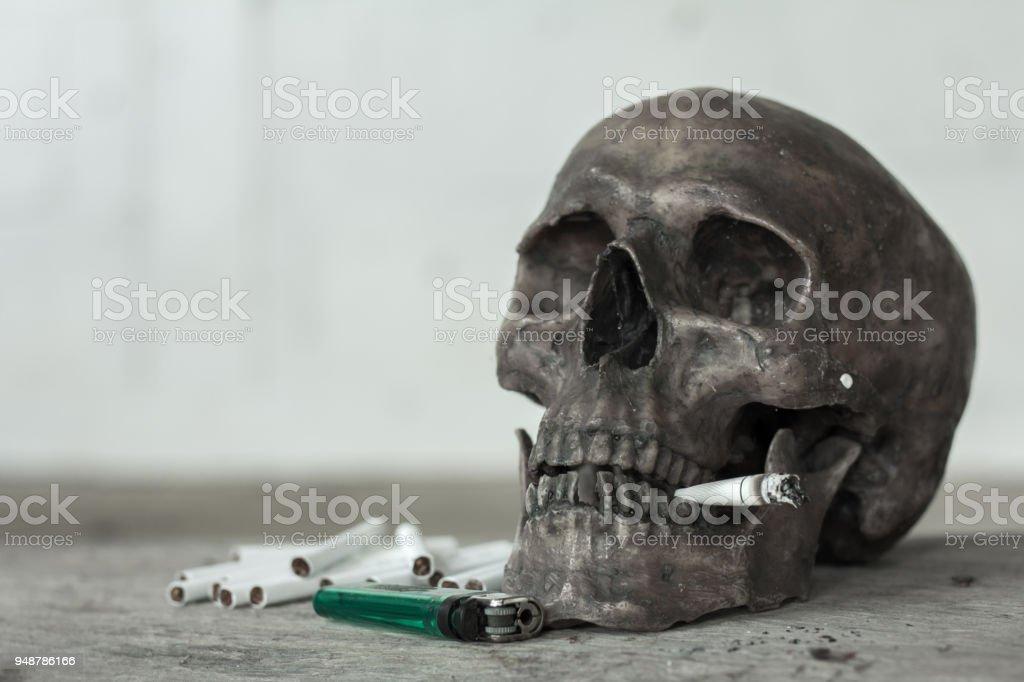 Cráneo humano fumando un cigarrillo, muerto a causa de fumar, dejar de fumar concepto. - foto de stock